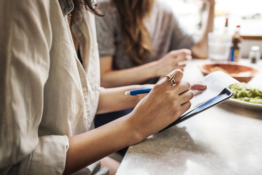 Midsection of woman writing on paper while sitting with friends in restaurant