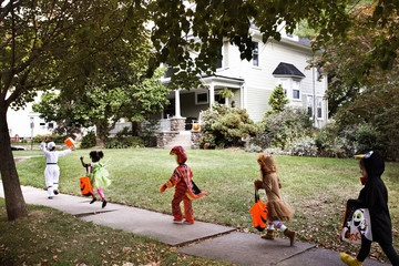Children wearing Halloween costumes running on pathway towards house during trick or treating