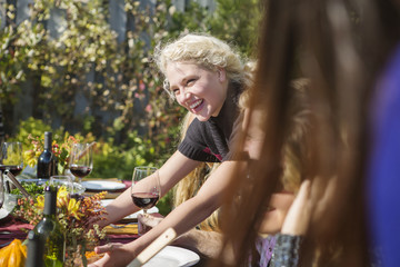 Cheerful woman with friend at outdoor table during garden party