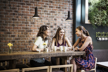 Happy friends having coffee at table by brick wall in cafe