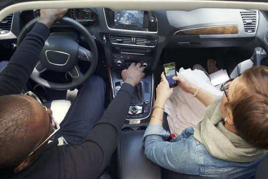 Woman looking map while man driving car