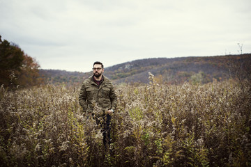 Man with hands in pockets standing on field amidst plants during winter