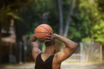 Rear view of man throwing basket ball while standing in court