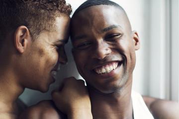 Close-up of smiling gay men at home