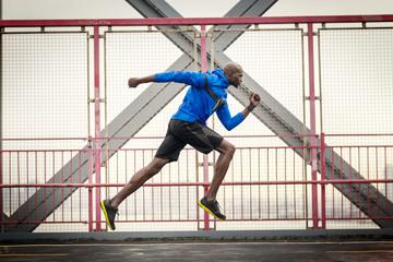 Confident man running at pedestrian walkway