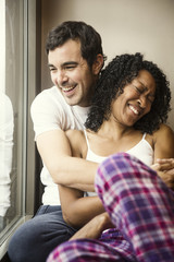 Cheerful couple embracing while sitting by window at home