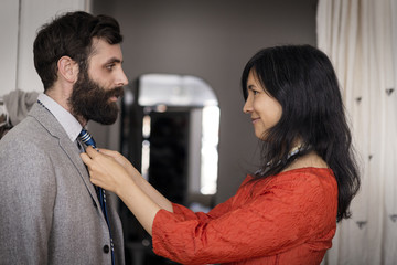 Smiling woman adjusting necktie on husband at home