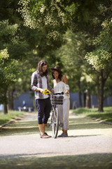 Happy couple standing with bicycle on footpath at park