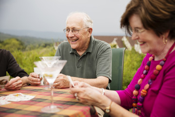 Smiling senior couple playing cards while sitting outdoors