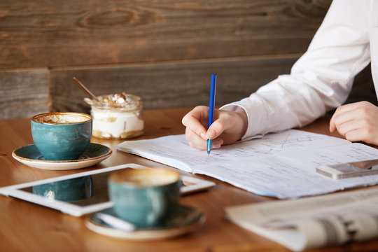 Selective focus. Close up view of freelancer making notes in her notebook with a pen, sitting at the wooden table spending morning at a cafe, working on project, using blank copy space tablet