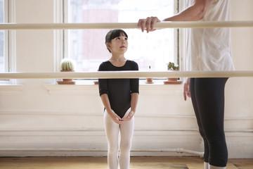 Cute ballerina looking at male teacher in ballet studio