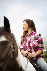 Teenage girl looking away while sitting on horse against sky