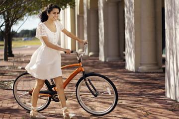 Happy teenage girl walking with bicycle on sunny day