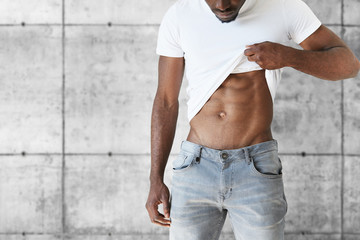 Cropped portrait of young black athletic man wearing stylish jeans and white T-shirt showing off his muscles. Attractive African male demonstrating his fit muscular body posing against gray brick wall