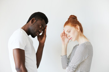 Sideways portrait of couple in disappointed pose in white studio. Caucasian girl resting her head on her hand as if thinking and solving the problem, African man also looking puzzled and stressed.
