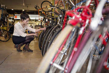 Woman examining bicycle while crouching in store