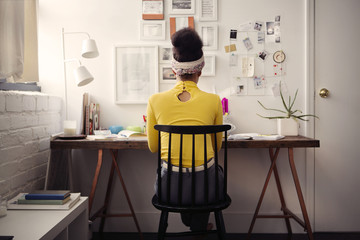 Rear view of woman sitting at table against papers on wall