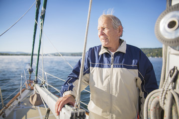 Thoughtful senior man standing in yacht on sea