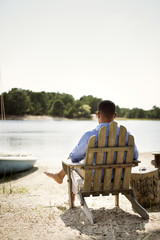 Rear view of man relaxing on adirondack chair at lakeshore