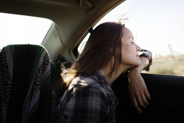 Side view of young woman travelling in car