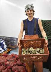 Portrait of man holding oyster container while standing in fishing industry