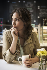 Thoughtful woman with coffee mug sitting at table in cafe