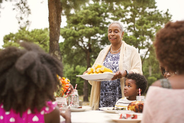 Woman serving corn to family sitting at table in backyard