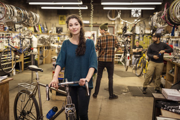 Portrait of woman holding bicycle while standing with coworkers in backgrounds