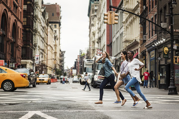 Smiling friends running while crossing road in city
