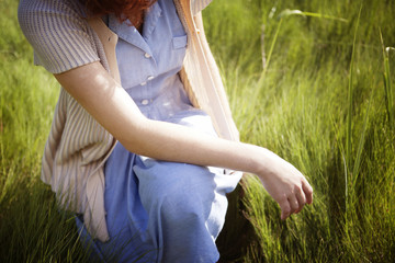 Midsection of woman crouching on grassy field
