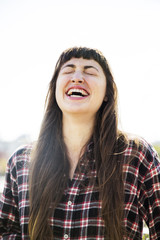 Cheerful woman laughing against clear sky