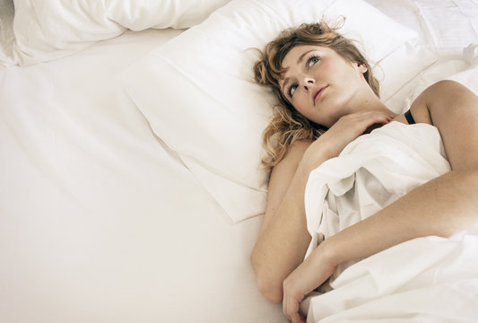 High angle view of thoughtful woman relaxing on bed at home