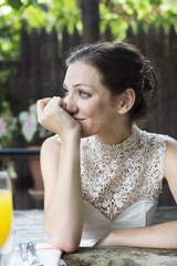 Woman with hand on chin looking away while sitting in restaurant