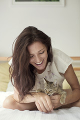 Woman looking at cat while sitting on bed