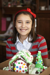 Portrait of smiling girl with gingerbread house