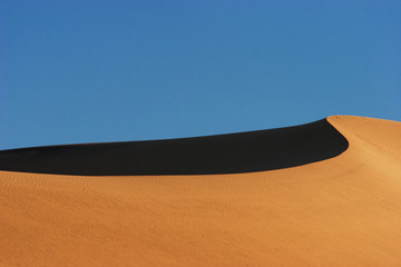View of sand dunes against clear blue sky