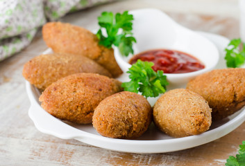 Kibbeh. Traditional Arabian meatballs with parsley in white plate on wooden background. Eastern cuisine. Selective focus