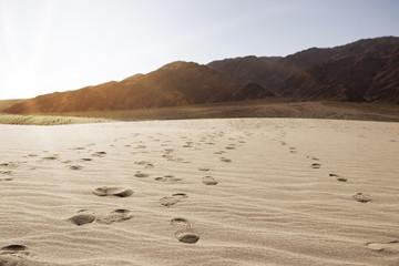 Footprints on sand against clear sky