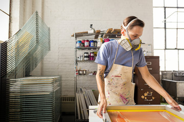 Worker wearing protective mask working on silk screen in workshop