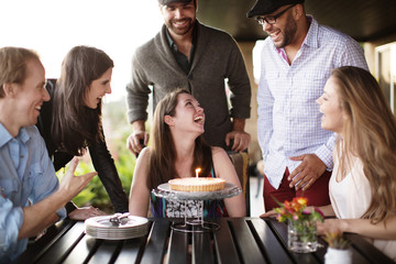 Group of smiling friends celebrating birthday outdoors
