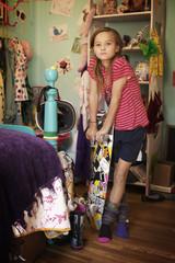 Girl (10-11) with skateboard in domestic room