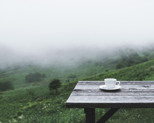 Coffee cup on wooden table against scenic view