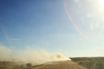 Dust on dirt road amidst field against blue sky during sunny day