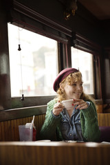 Woman with coffee cup looking away while sitting in restaurant