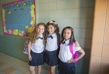 Portrait of schoolgirls standing in corridor