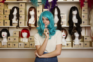 Young woman trying on blue wig