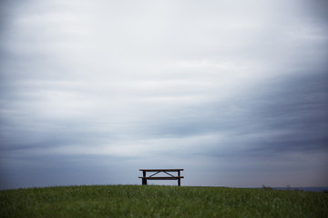 Bench with table on grass under overcast sky