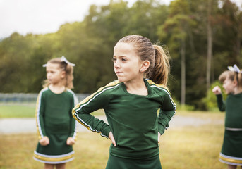 Girls looking away while standing in sports field