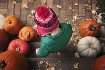 Little boy in knit hat on wooden steps among pumpkins