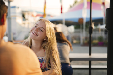 Smiling teenager sitting with boyfriend at amusement park